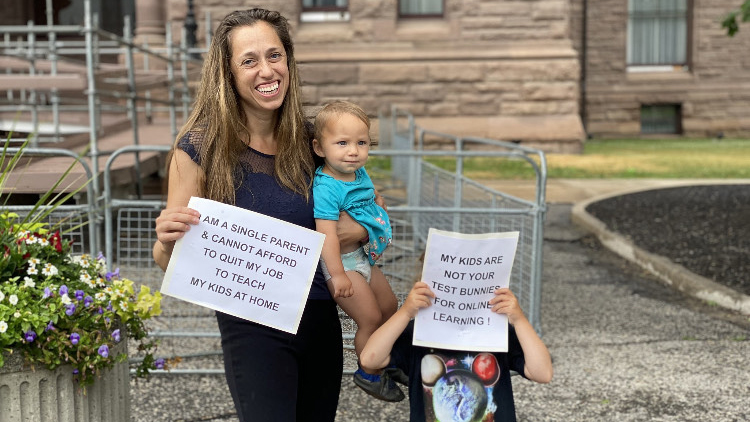 "The author and her two children at a protest at Queen's Park, holding a sign that says ""I am a single parent and cannot afford to quit my job to teach my kids at home"""