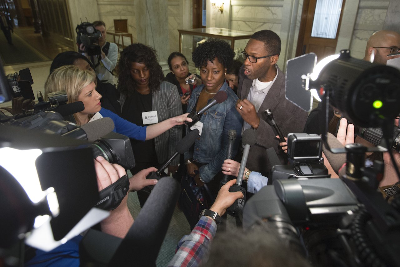 A photo of Charline Grant in the middle of a media scrum