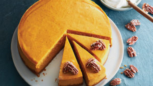 round pumpkin cheesecake with three slices cut and waiting to be served