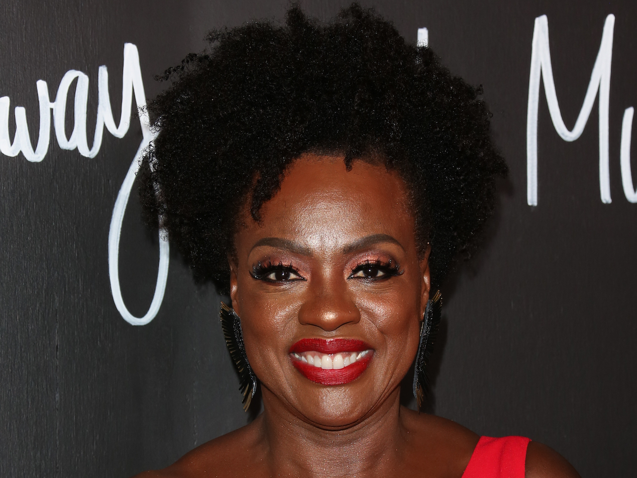 A photo of Viola Davis with natural hair and a red lip