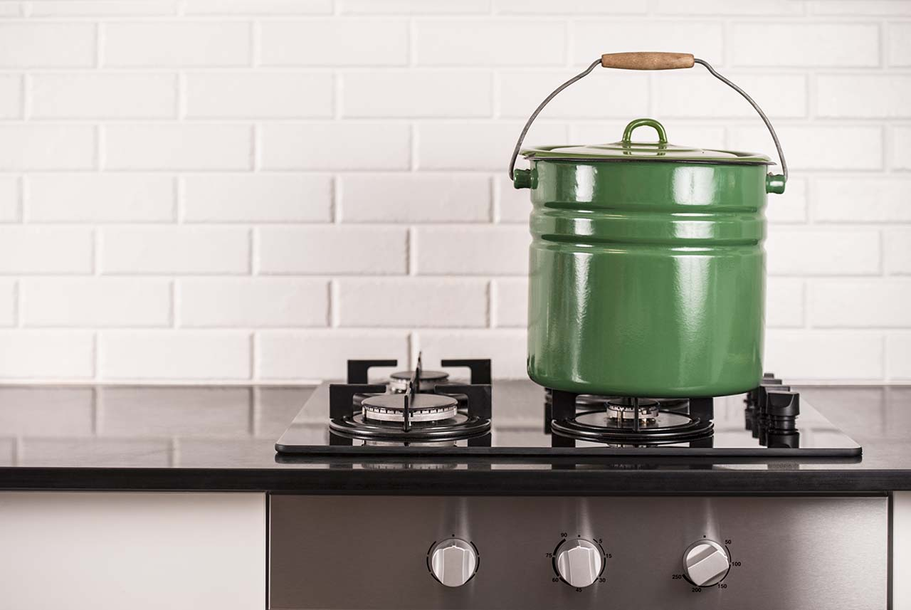 A green home beer brewing pot on a stove for a piece about making beer at home