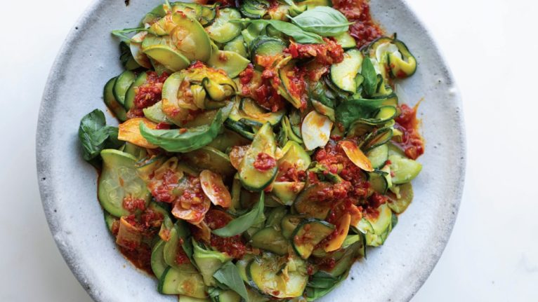 a dish of sliced zucchini, harissa and lemon