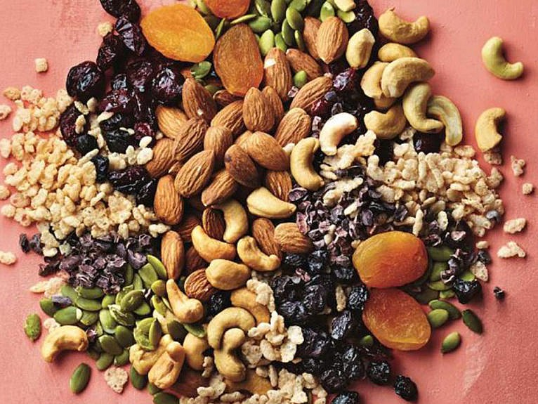Bulk nuts and dried fruit on pink background
