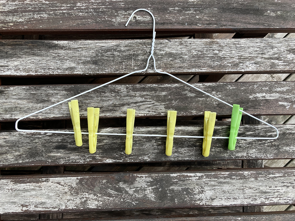 A homemade mask drying rack, using clothes pins and a coat hanger