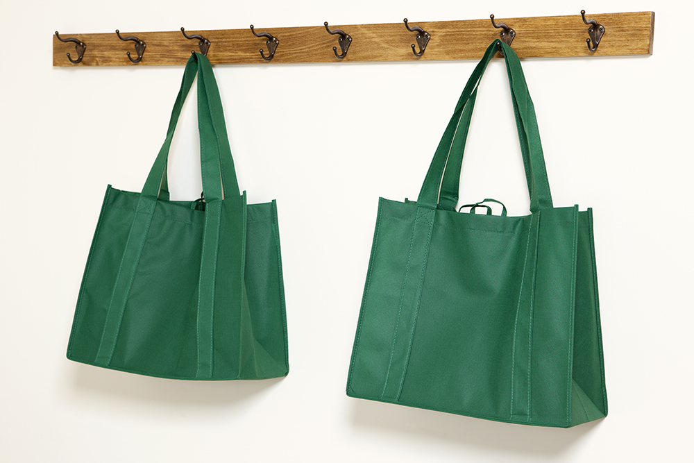 Two green shopping bags hanging from a rack for mask storage ideas