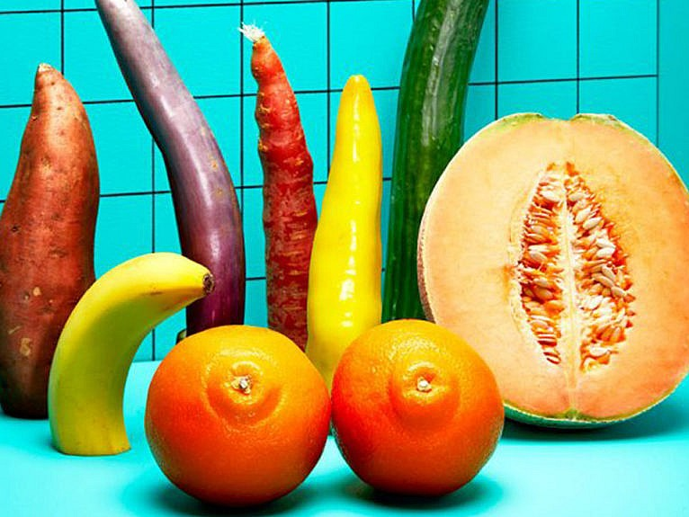 a bunch of fruits and veggies laid out on a blue counter, all cut in half, looking very phallic.