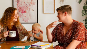 two women sit at a kitchen table with a toddler