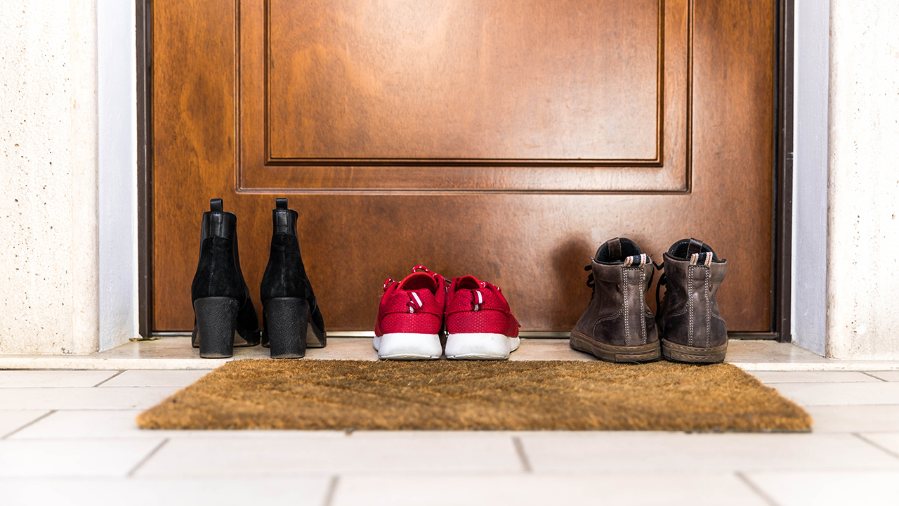 Three pairs of shoes sitting outside in front of a front door for a piece on whether to wear shoes inside