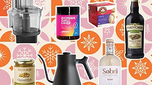a tea kettle, bottle of gin, chili oil, tea and blender on a vibrant background