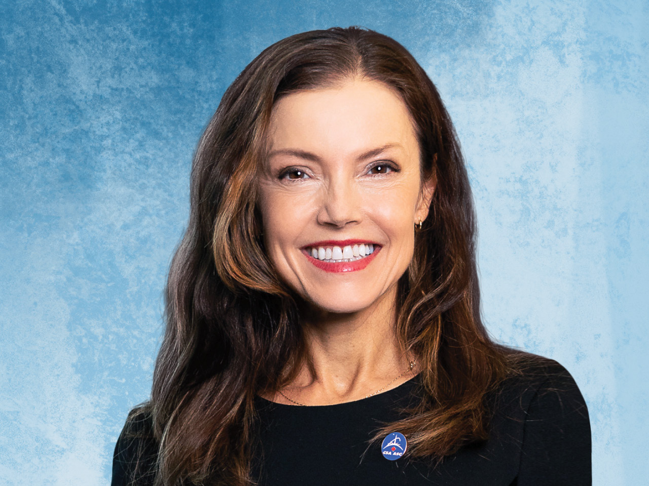 A portrait of Lisa Campbell, president of the Canadian Space Agency, on a blue background