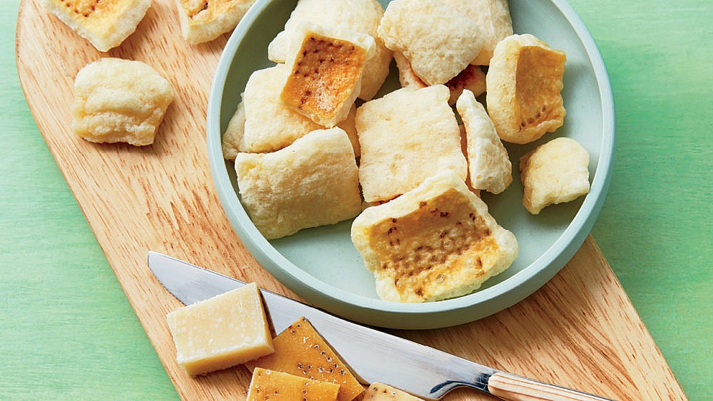 Parmigiano-Reggiano rind croutons on a plate and wooden board.