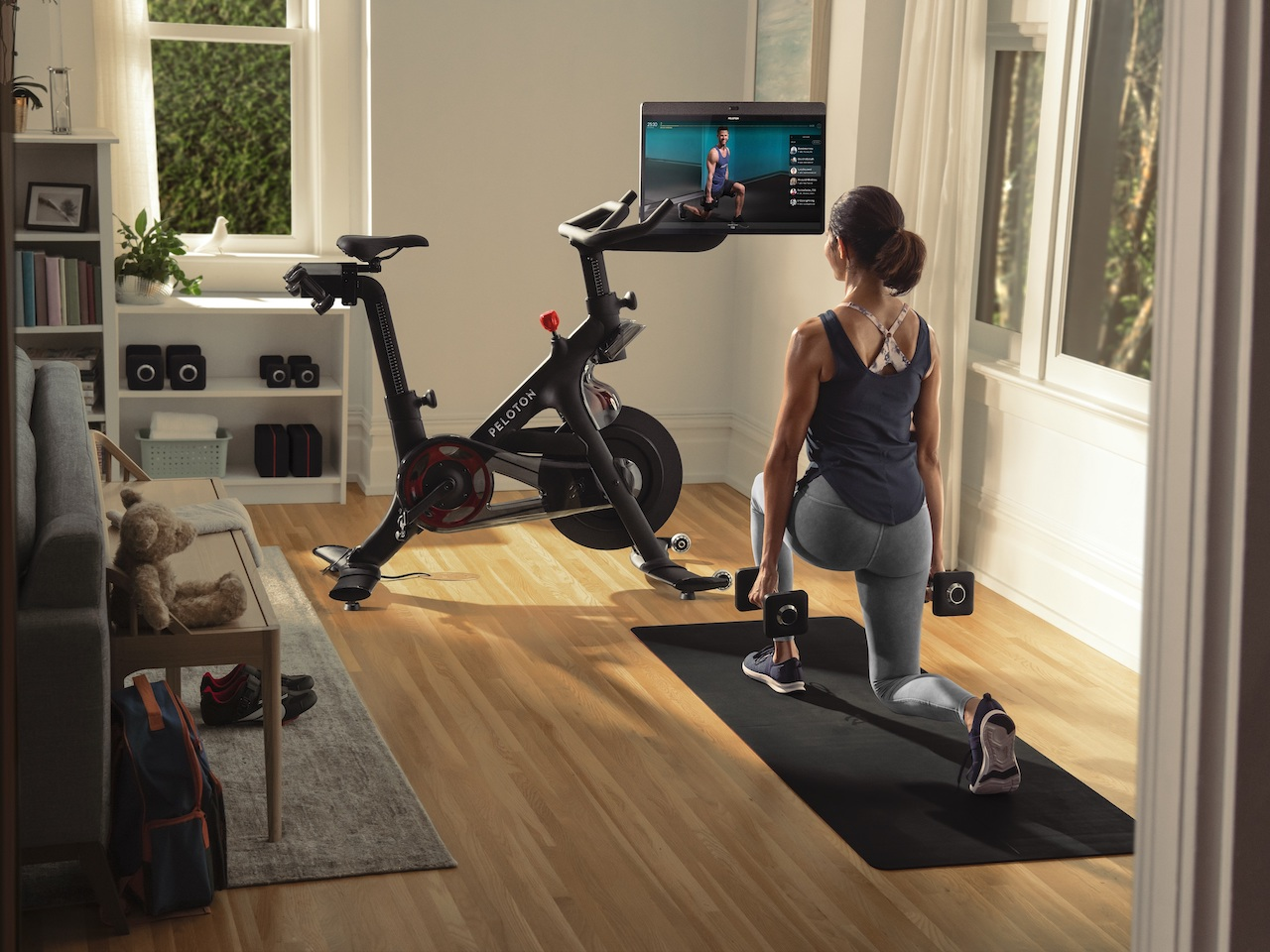 A woman doing a strength workout on the floor while looking at her Peloton screen