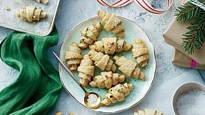 Pistachio-lemon rugelach cookies on round aqua-green plate