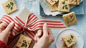 Savoury shortbread cookies on plate, next to brown-paper-wrapped gift with hands tying ribbon