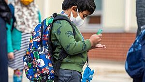 A student uses hand sanitizer as he arrives at school in September 2020 (Carlos Osorio/Reuters)