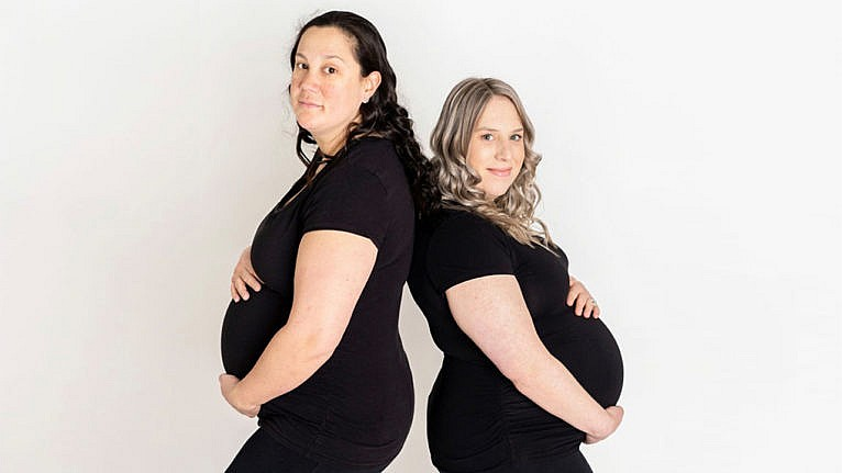 The two moms, pregnant, post back to back