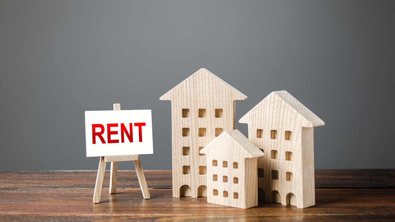 Three figures of houses and an easel with the word rent for a piece on how to negotiate your rent