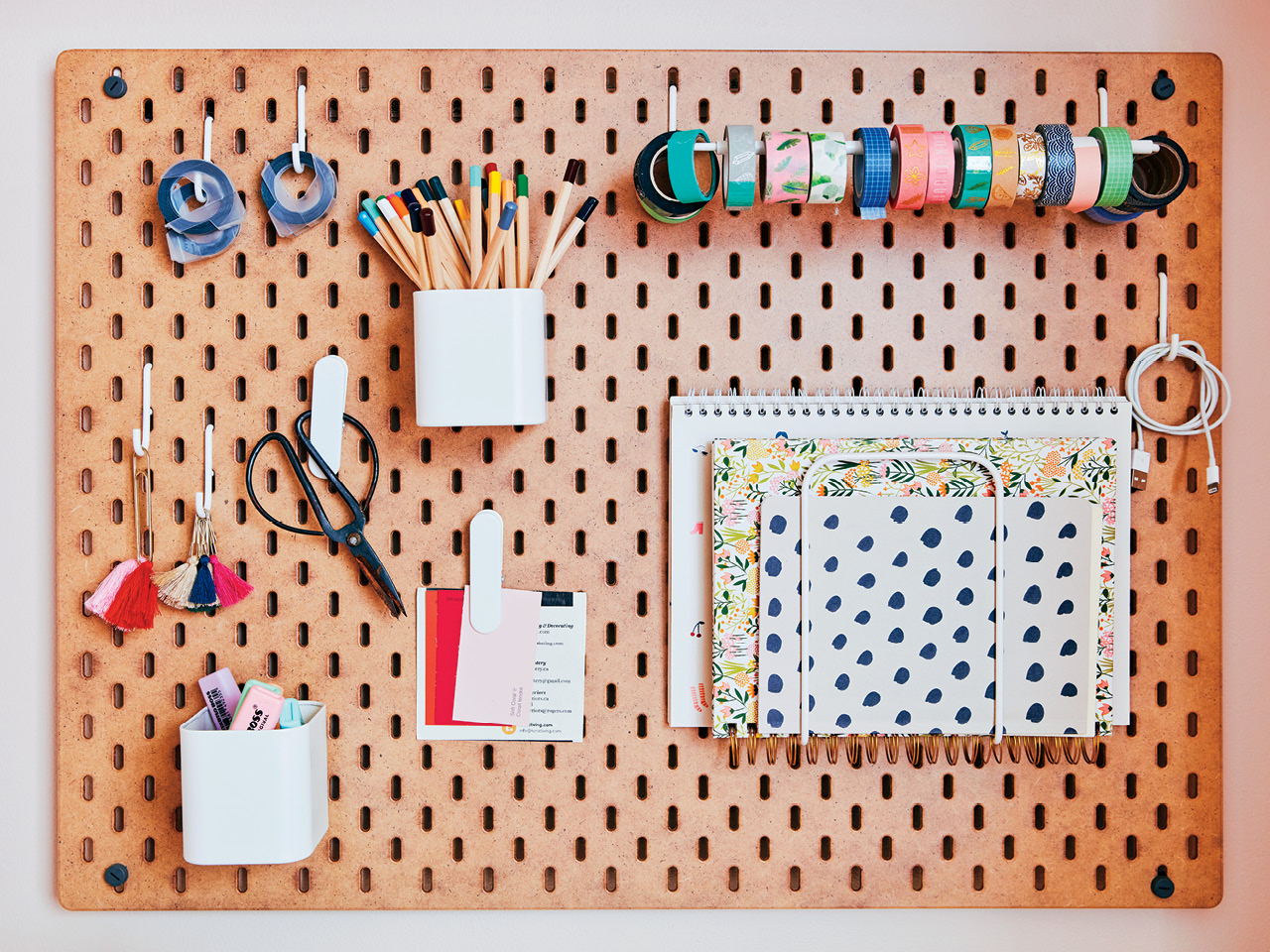 A brown pegboard hanging on a wall holds various stationary items such as scissors, pens, notebooks and tape.