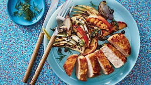 Pan-fried pork chops with roasted apples and fennel on blue dinner plate with dill garnish