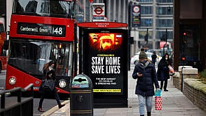A digital display at a bus station warns pedestrians of the new strain of coronavirus in central London on January 8, 2021