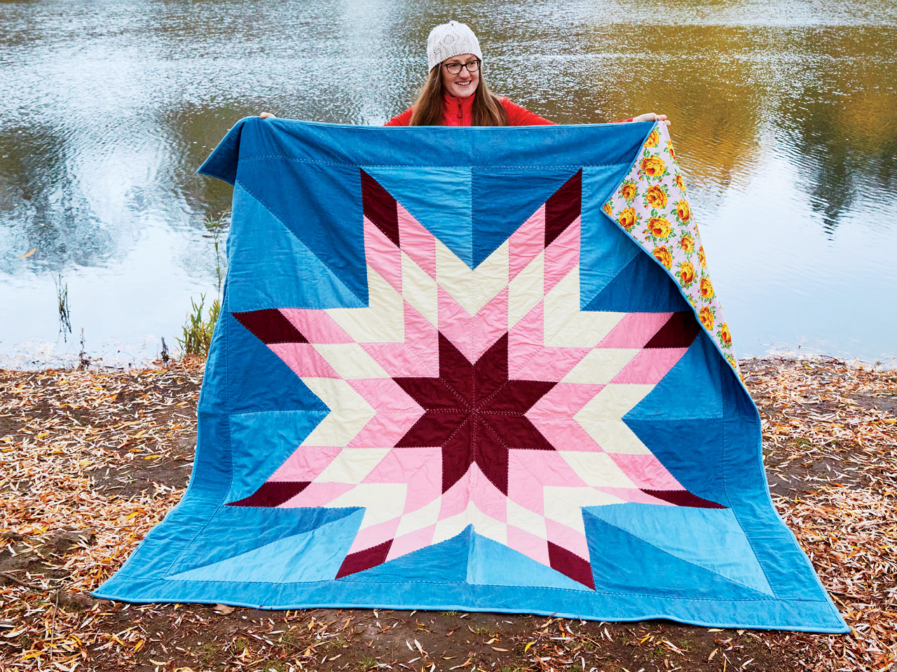 The author holds her pandemic quilt, a large mix of denim and fabric