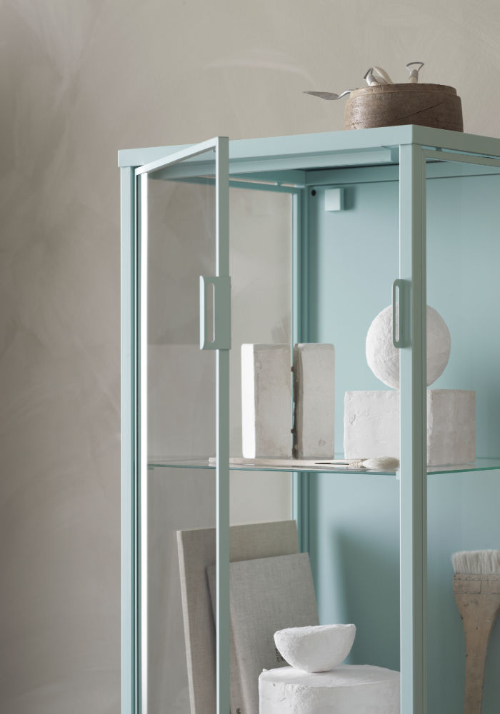 A soft baby blue glass cabinet with white ornaments on the inside