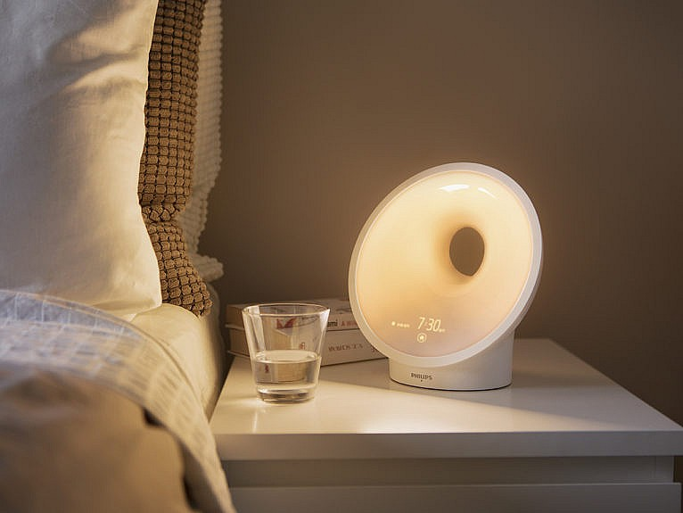 Wake-up light on white side table to the right of a bed.