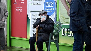 Older man wearing a mask and sitting in a chair waiting in line.