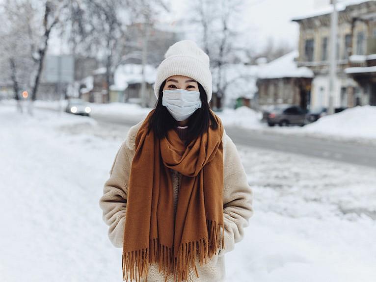 Woman stands on the snow, wearing a mask, hat and a scarf.