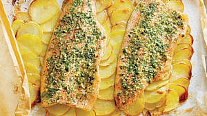 Baked rainbow trout fillets with tarragon and parsley herb mix, and thin potato slices