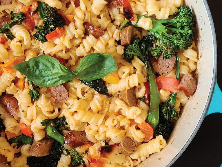 Pot of creamy pasta with sausage, tomato and broccolini.