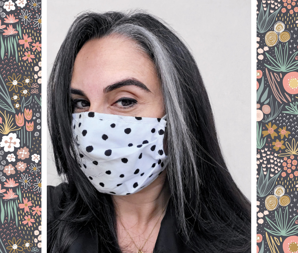 A photo of a woman with dark brown hair and a small grey streak, wearing a white face mask with black polka dots.