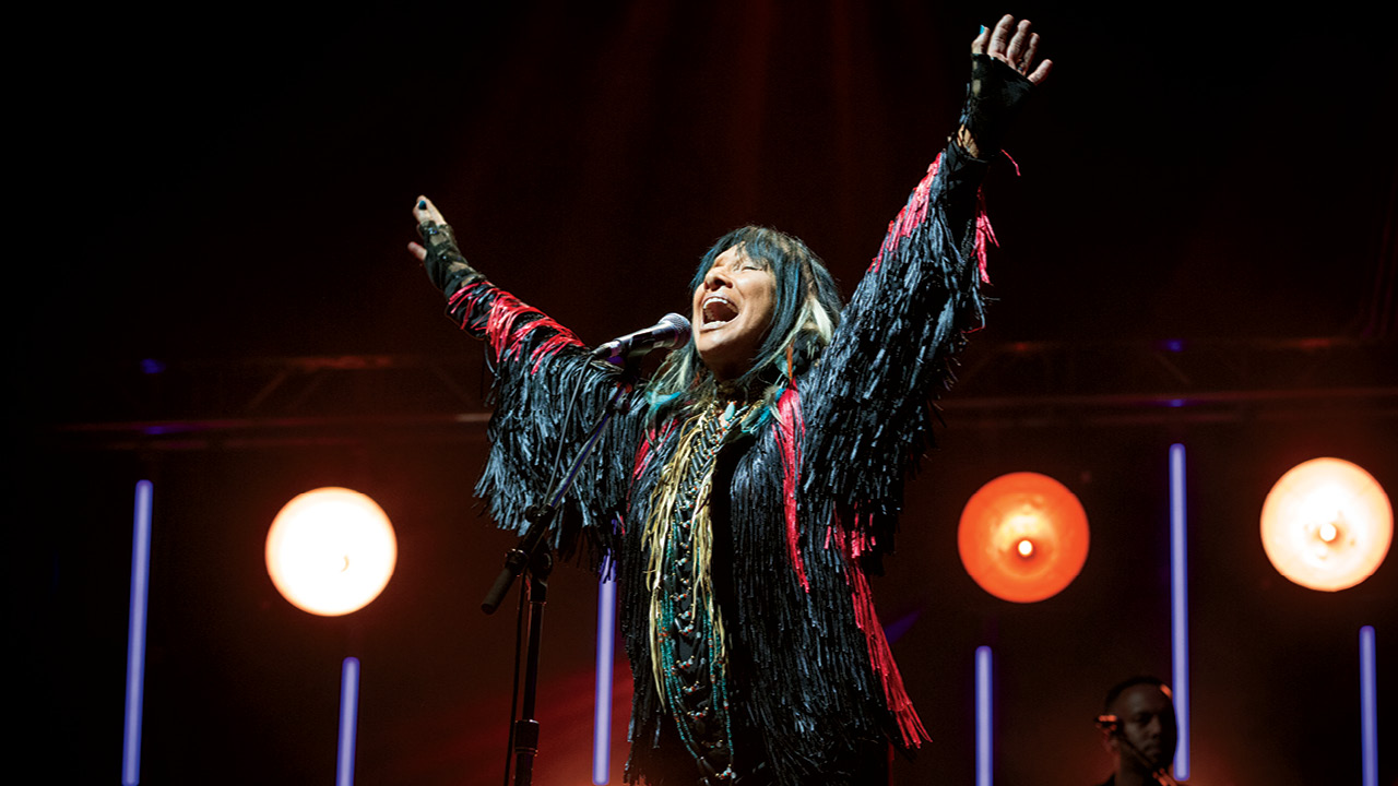 A photo of Buffy Sainte-Marie in concert, arms upraised and singing.