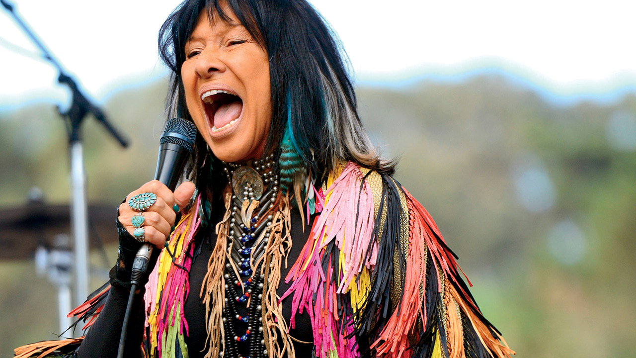 A photo of Buffy Sainte-Marie performing outdoors in a multi-coloured fringe top.