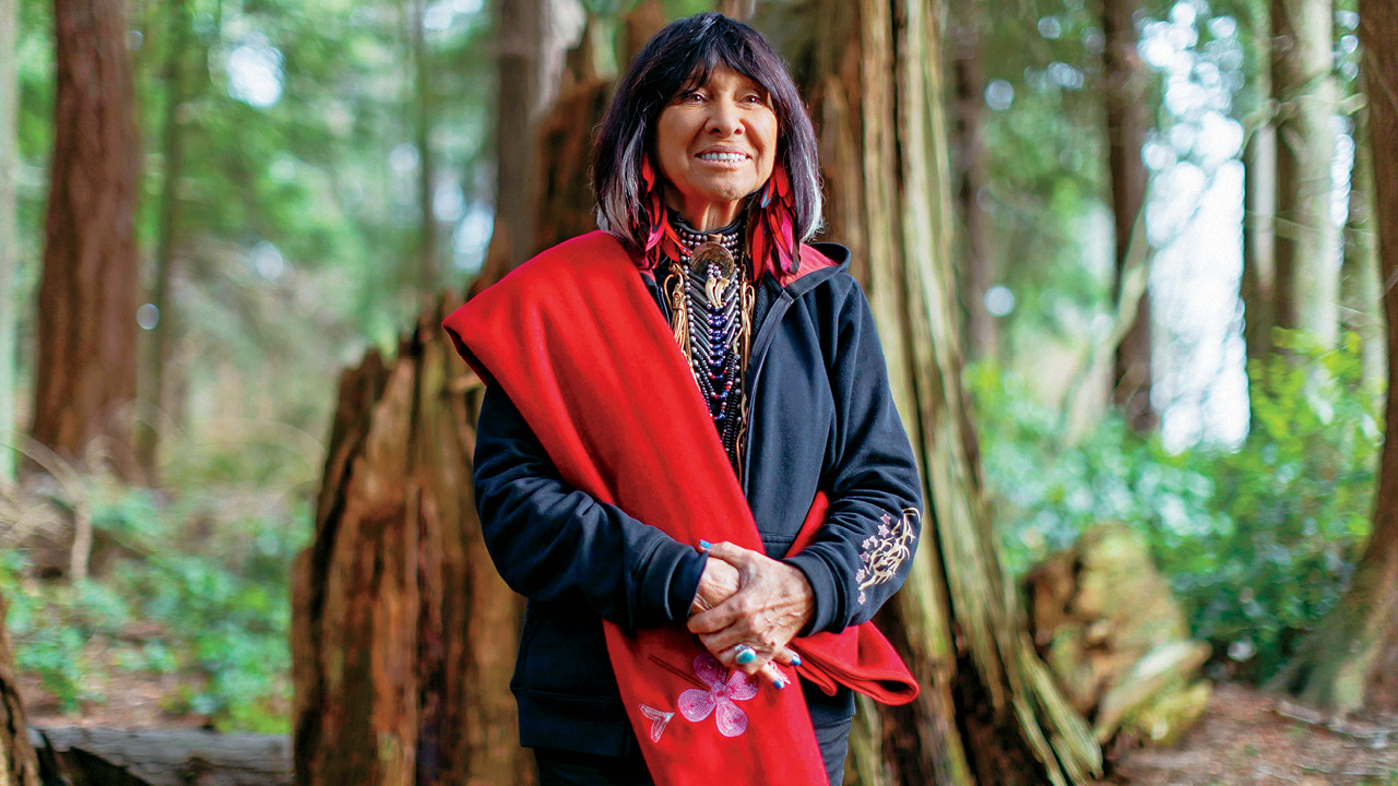Buffy Sainte-Marie wearing a red sash standing in a British Columbia forest