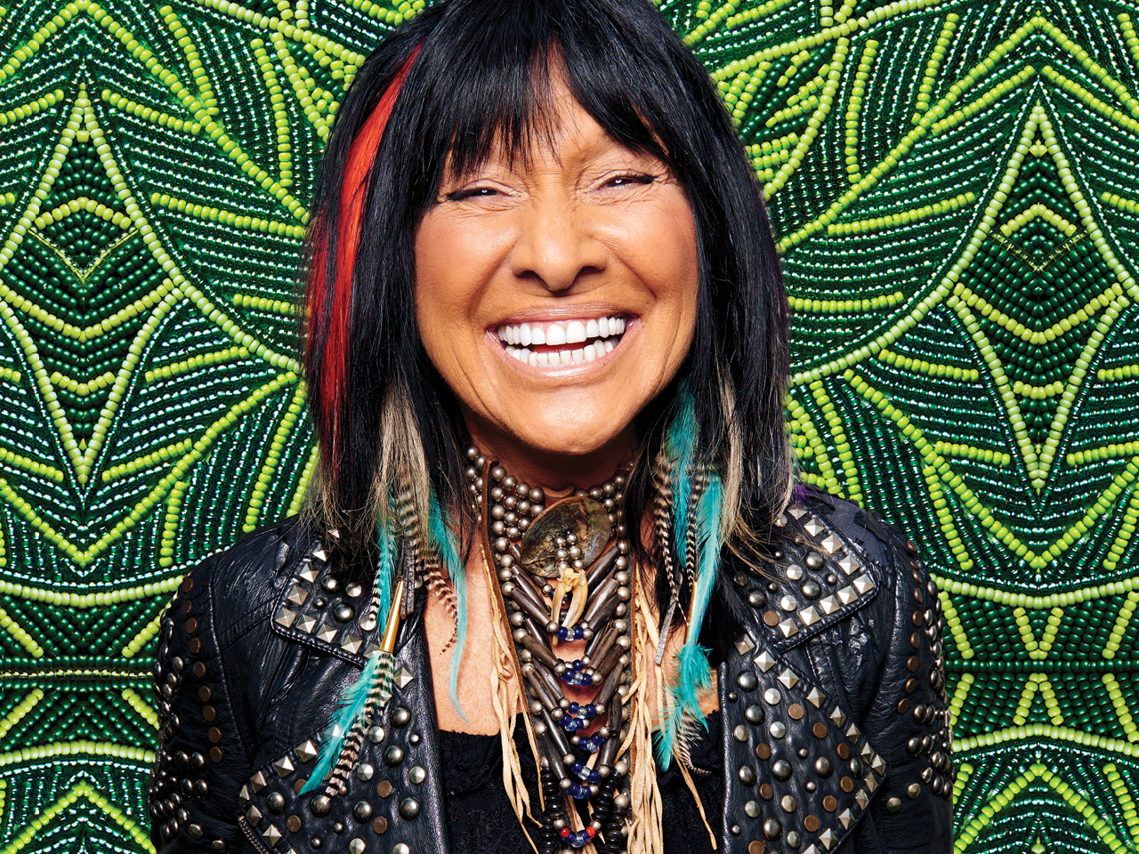 A photo of Buffy Sainte-Marie against a green beaded backdrop by Katie Longboat
