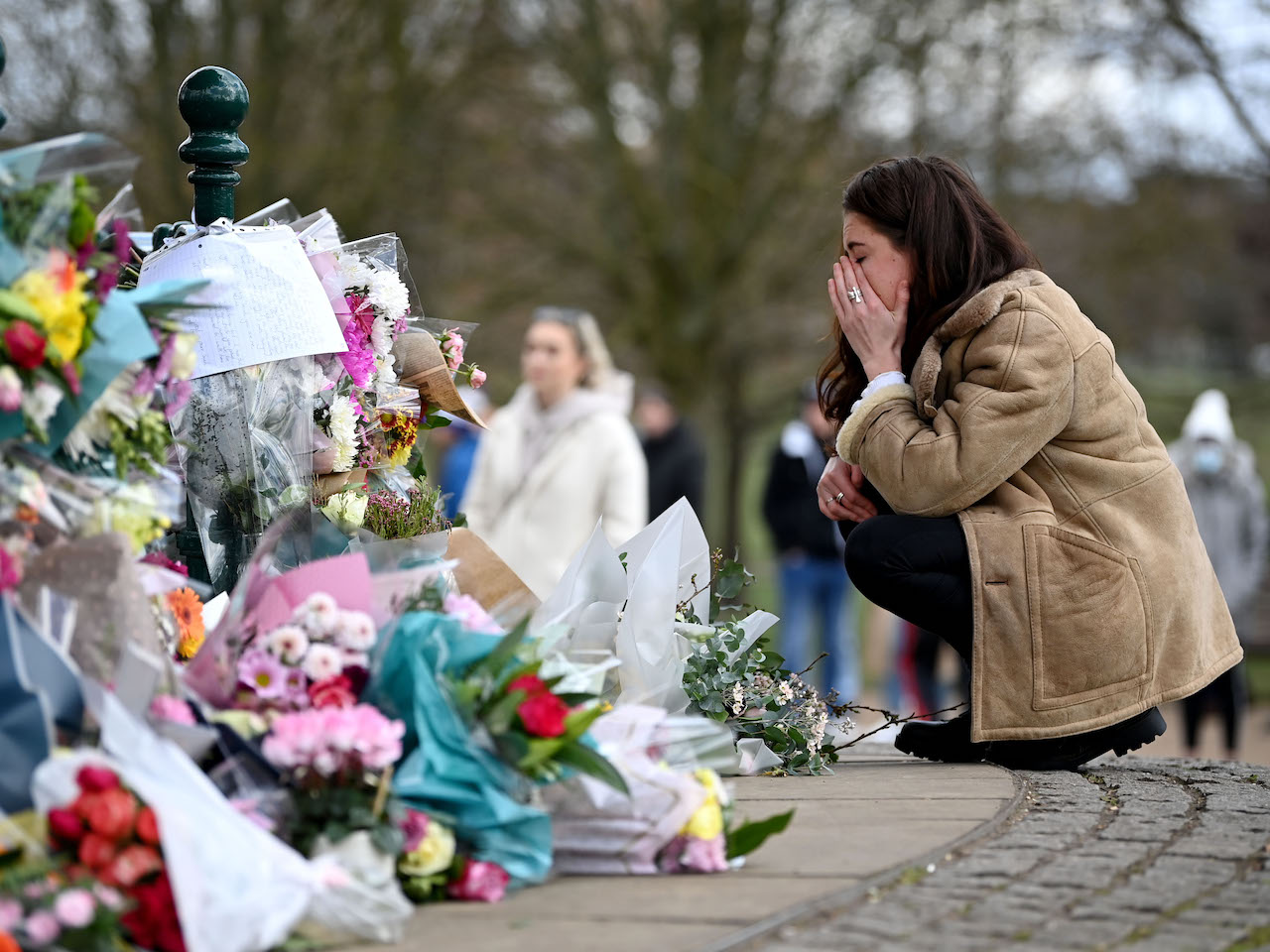 A woman reacts as she lays flowers in tribute to Sarah Everard at the bandstand on Clapham Common on March 13, 2021 in London, United Kingdom. Vigils are being held across the United Kingdom in memory of Sarah Everard. Yesterday, the Police confirmed that the remains of Ms Everard were found in a woodland area in Ashford, a week after she went missing as she walked home from visiting a friend in Clapham. Metropolitan Police Officer Wayne Couzens has been charged with her kidnap and murder.