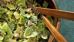 A bowl of classic caesar salad, with salad tongs and croutons
