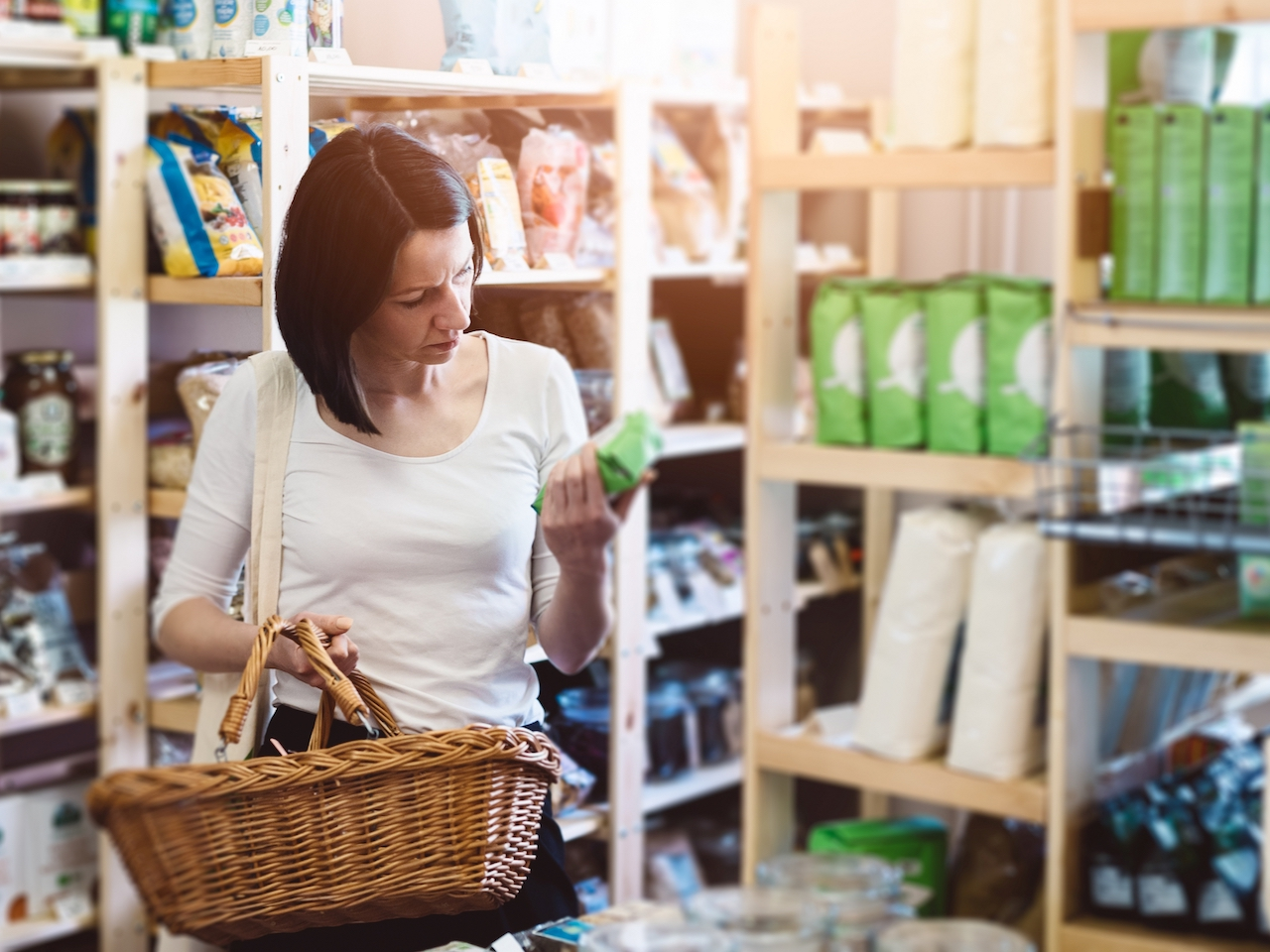 A photo of a woman scrutinizing the label on a package at a natural food store