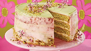 Pistachio cake with orange blossom icing on a pink plate infront of a floral backdrop