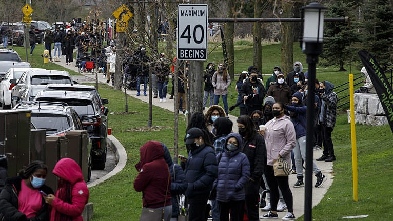 Residents of Toronto's Jane and Finch neighbourhood, in the M3N postal code, line up at a pop-up COVID-19 vaccine clinic on Saturday, April 17, 2021. THE CANADIAN PRESS/Cole Burston