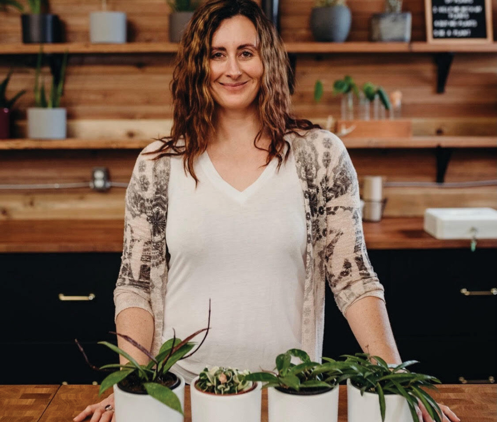 A woman photographed with her plants for an article on plant delivery in Canada.