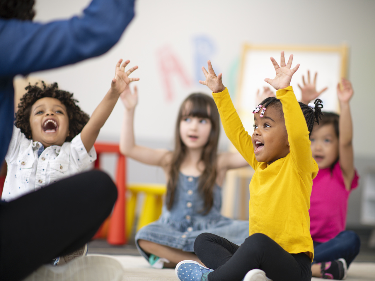 A group of preschool students is sitting with their legs crossed on the floor in their classroom. The mixed-race female teacher is sitting on the floor facing the children. The happy kids are smiling and following the teacher's instructions. They have their arms raised in the air.