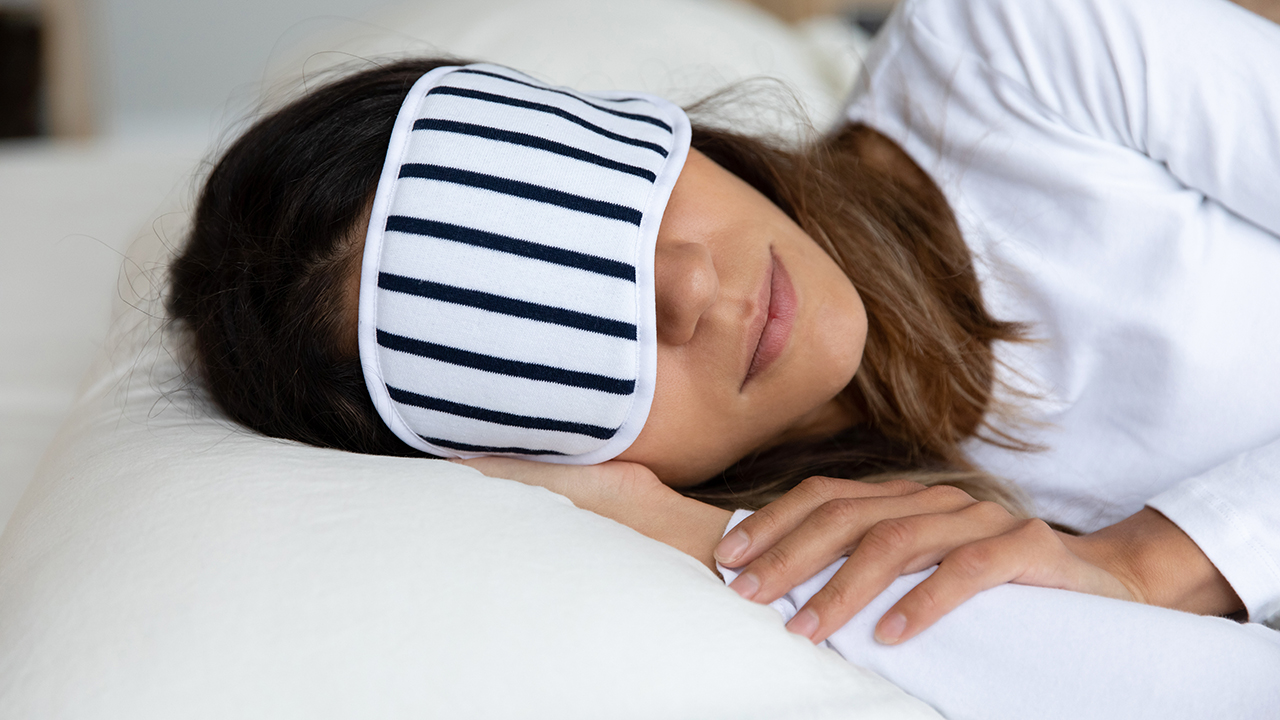A woman wearing a striped sleep mask lying on her side on a pillow for a piece on the best pillows for sore necks and neck pain