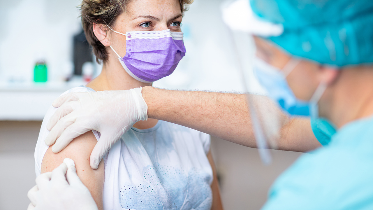 Female patient with protective face mask waiting for vaccination, doctor in surgical gloves disinfecting her arm