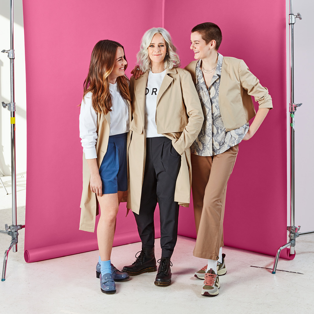 Three women against a pink background wearing updated basics trench coat for an article on spring 2021 fashion trends.
