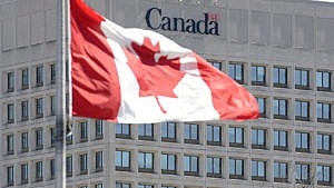 The Canadian flag waving in front of the The facade of the headquarters of the Department of National Defence in Ottawa.