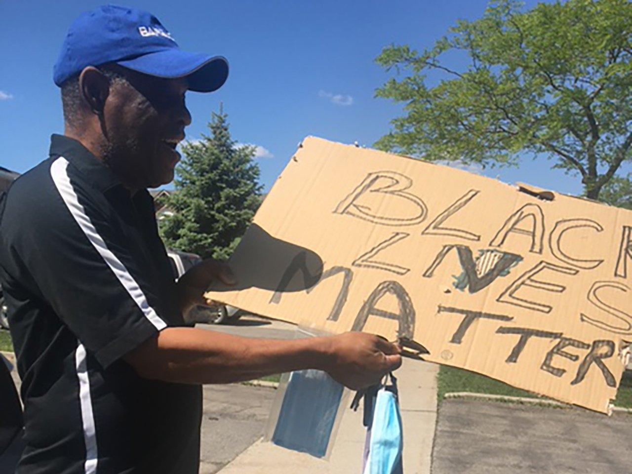 An older Black man holds a cardboard Black Lives Matter sign
