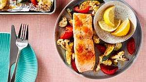 one-pan roasted salmon and vegetables on a plate with two lemon wedges