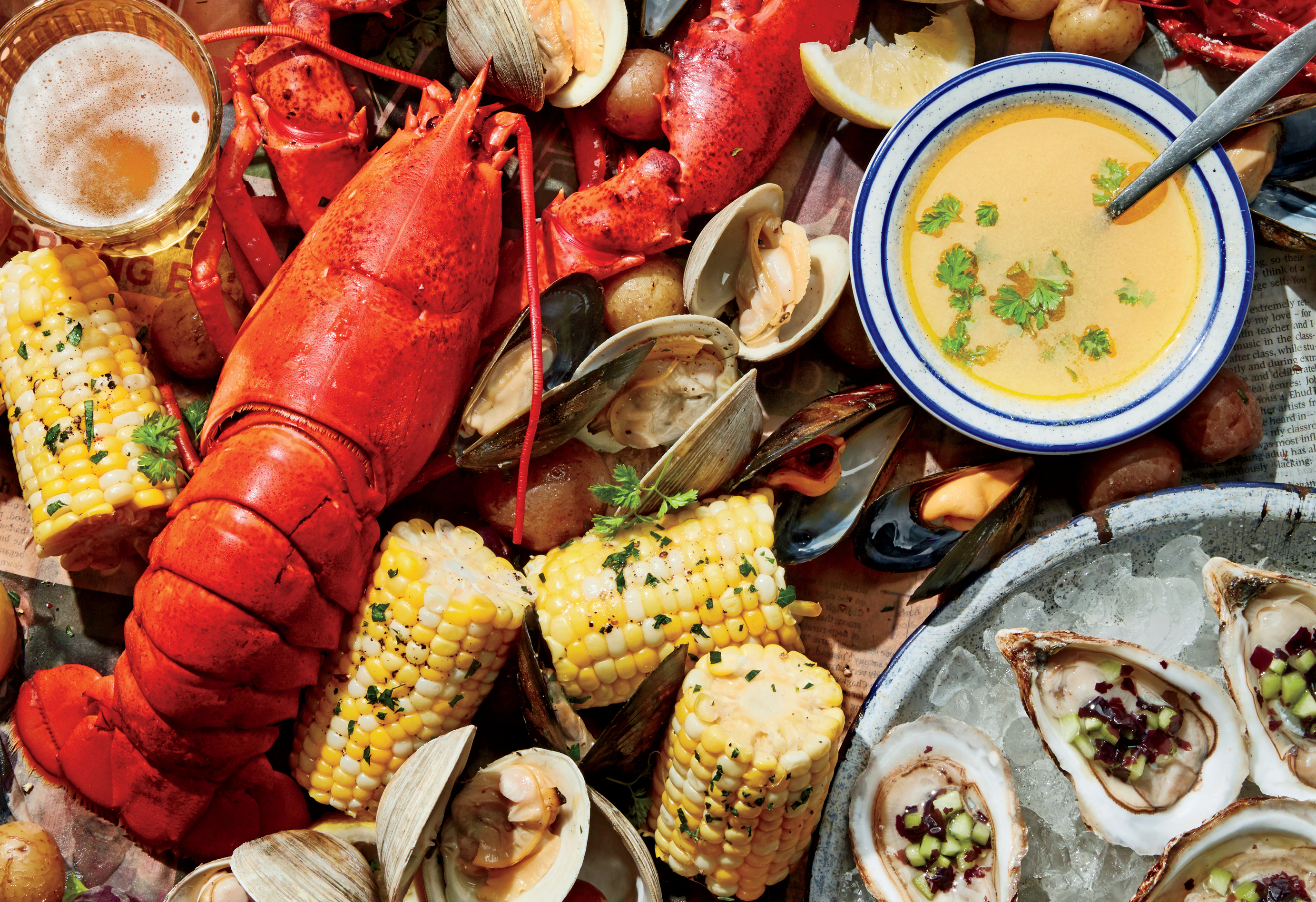 Lobster, clam, mussels, corn cobs, potatoes and beer on top of newspaper